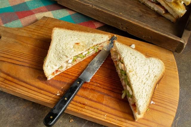 Накрываем ингредиенты ломтиком хлеба и разрезаем пополам по диагонали