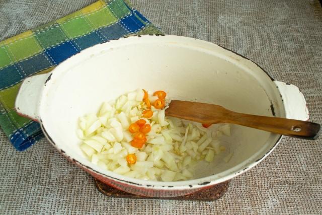 В растопленный жир кладём лук, затем добавляем чеснок и перец чили