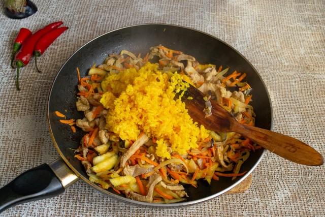 Выкладываем в сковородку отваренный рис