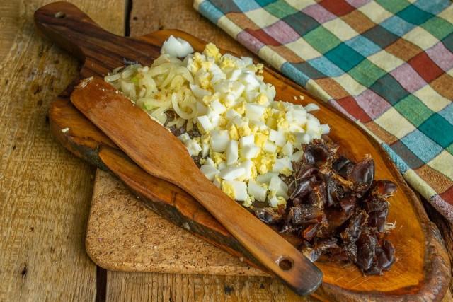 Обжариваем и приправляем лук, рубим вареные яйца и измельчаем финики