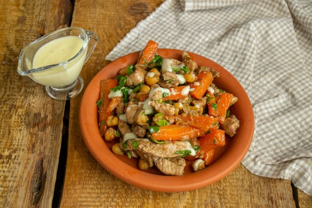 Выкладываем нут с мясом на тарелку, поливаем сырным соусом и сразу подаём на стол