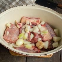 На мясо высыпаем примерно половину нарезанного лука