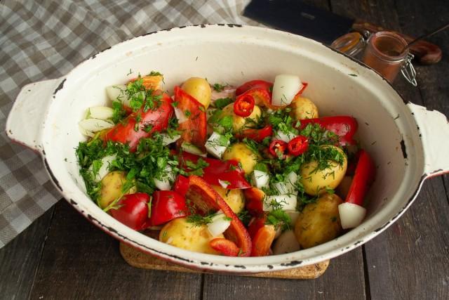 Посыпаем картошку и перец нарезанным луком и зеленью, добавляем чили