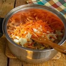 Добавляем в кастрюлю лук и морковь, обжариваем овощи на среднем огне 10 минут