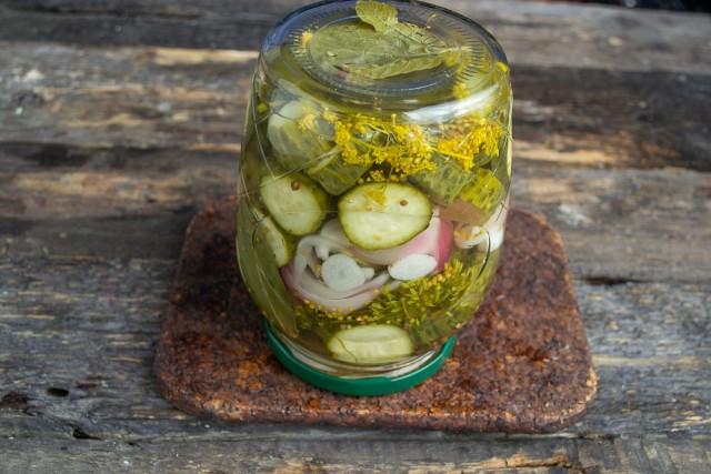 Пастеризуем банки с маринованным салатом из огурцов, после остывания убираем на хранение