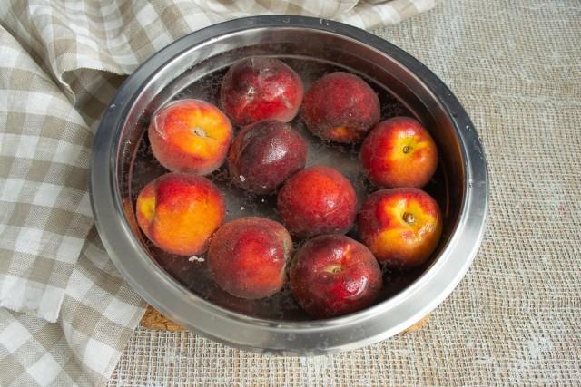 Наливаем к персикам кипящую воду, через несколько минут перекладываем в ёмкость с холодной водой