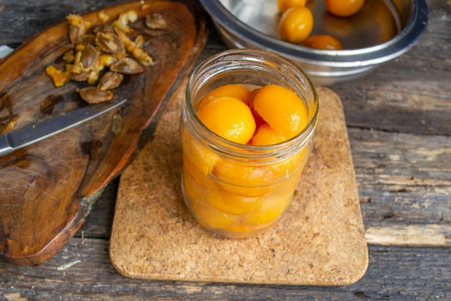 Укладываем абрикосы в стерилизованную банку до самого верха, вливаем кипящую воду, оставляем на несколько минут