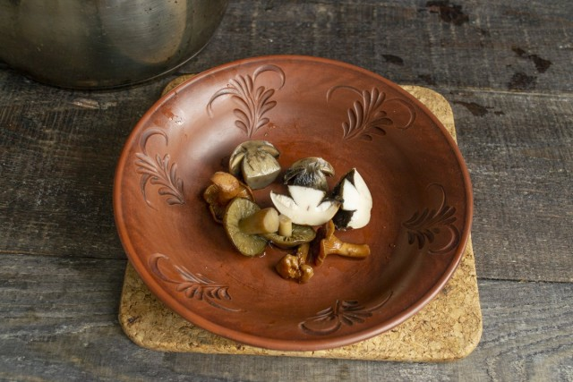 На дно тарелки кладём немного варёных грибов