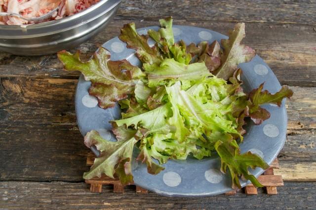 На дно тарелки кладём листочки салата