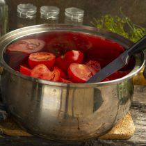 Разрезаем томаты пополам, кладём в кастрюлю с толстым дном, на дно наливаем немного воды