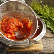 Распаренные томаты перекладываем на сито с мелкими ячейками, протираем ложкой