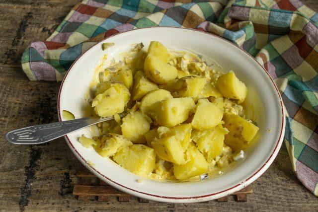 Крупно нарезаем отваренный картофель и кладём в миску с соусом