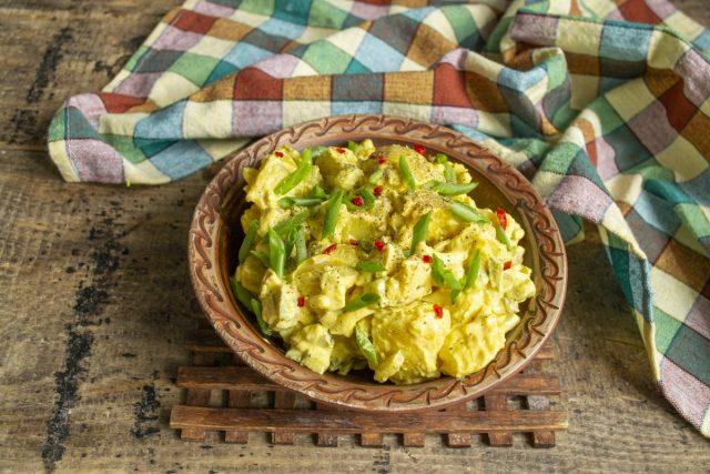 Выкладываем картофель в салатницу, посыпаем чили и зелёным луком