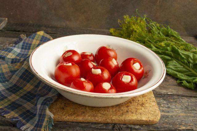 В подготовленные помидоры вкладываем чеснок