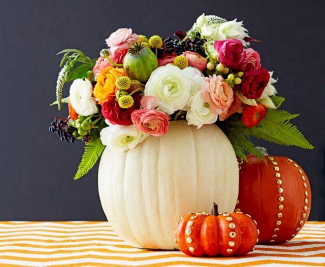 Композиция из свежих цветов и листьев, которая красуется не в обычной вазе, а в тыкве — красочный элемент осеннего декора