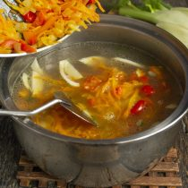 Добавляем обжаренные овощи, доводим суп до кипения, убавляем нагрев и закрываем крышкой