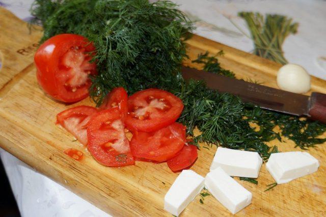 Нарежьте зелень, томаты, чеснок и сыр небольшими кусочками