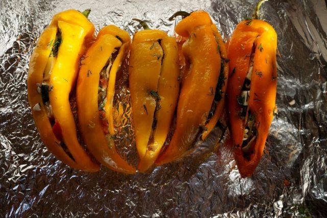 Выложите перцы на противень, покрытый пищевой фольгой, и заполните начинкой