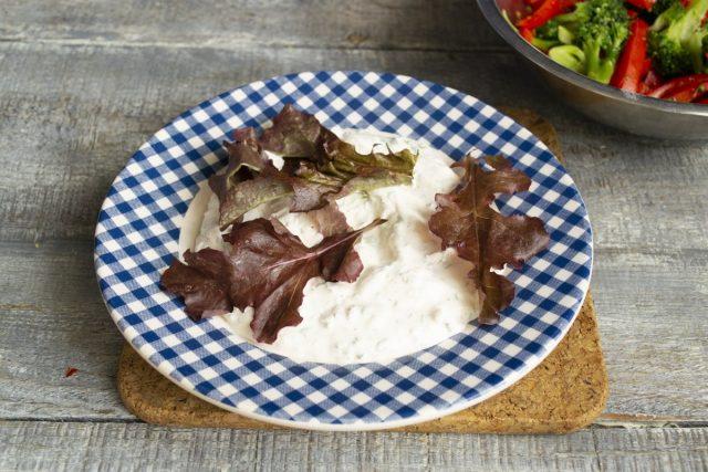 На тарелку выкладываем порцию соуса, сверху несколько листочков салата