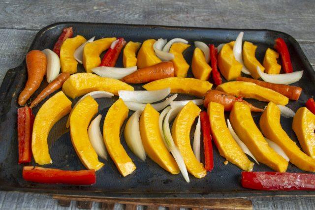 Выкладываем овощи между тыквенными ломтиками, ставим противень в разогретый духовой шкаф