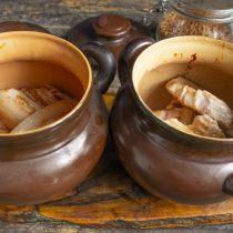 На дно горшочка кладём лук и морковь, выкладываем ломтики обжаренного мяса