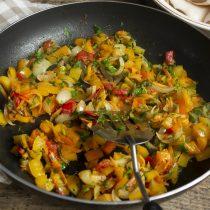 Добавляем морковь и помидор в сковороду, через 10 минут кладём зелень и приправляем