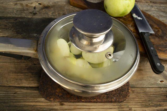 Наливаем в сотейник 2-3 ст. л. воды, кладём яблоки, закрываем крышкой и ставим на плиту