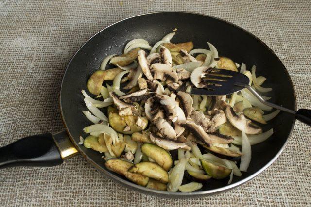 К обжаренным овощам добавляем нарезанные грибы, посыпаем солью, тушим 10 минут
