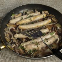 Возвращаем колбаски в сковородку, добавляем тимьян и розмарин. Готовим без крышки примерно 15 минут