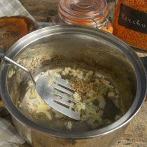 Достаем лук. Кладём в кастрюлю измельченный чеснок, насыпаем семена кориандра