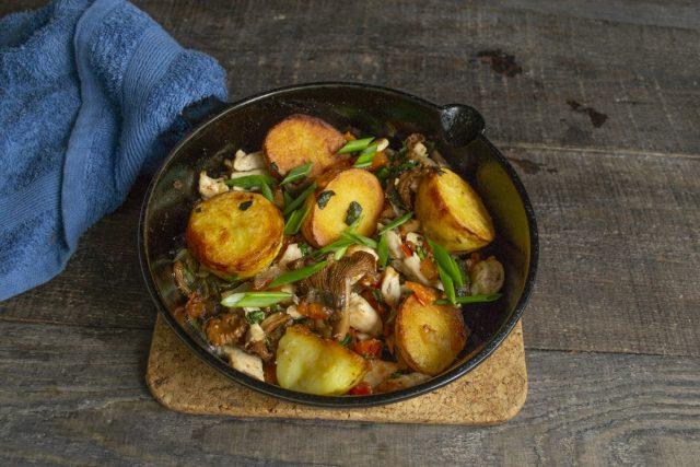 Выкладываем картошку с грибами и курицей в порционную сковородку и посыпаем зелёным луком