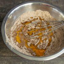 Вливаем жидкие ингредиенты в миску с мукой и какао, перемешиваем и добавляем масло. Замешиваем тесто