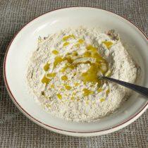 Добавляем оливковое масло, смешиваем ингредиенты и вымешиваем тесто