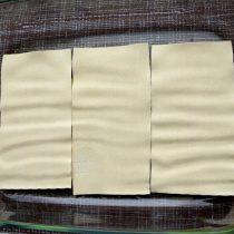Выкладываем на смазанное дно блюда для выпечки несколько сухих листов лазаньи в один слой