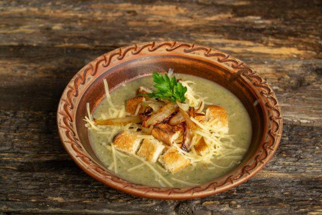 Добавляем поджаренный лук и зелень. Вкусный грибной крем-суп с гренками готов