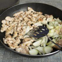 Переворачиваем кусочки курицы лопаткой, добавляем лук