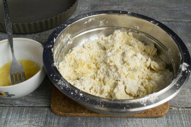 Смешиваем яйцо с солью. В миску с маслом добавляем муку и разрыхлитель, растираем в крошку