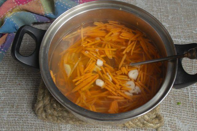 В кипящую воду кладём нарезанную морковь, имбирь и чеснок. Бланшируем овощи 3 минуты