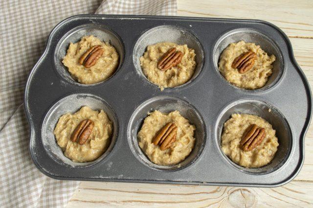 Выкладываем тесто в формы, заполняем их примерно на 2/3 от объёма, сверху кладём половинки пекана
