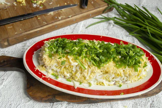 На гребешок салата наносим слой майонеза, посыпаем зелёным луком, чуть прижимаем