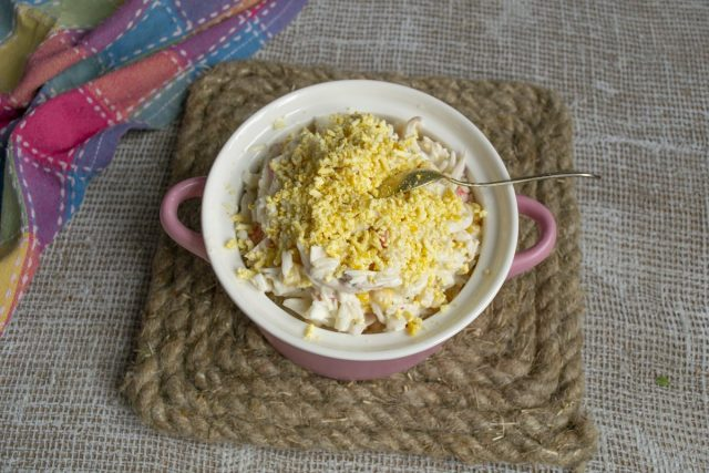 Выкладываем салат горкой, посыпаем тёртым желтком