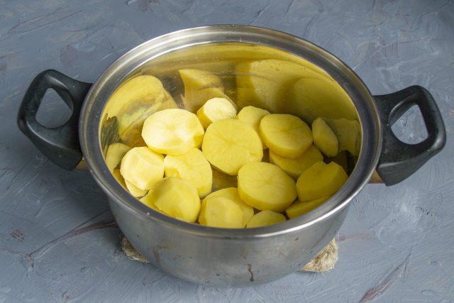 Картофель чистим от кожуры, нарезаем толстыми кружочками и кладём в кастрюлю