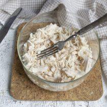 Варёную куриную грудку разбираем на волокна, кладём в салатницу