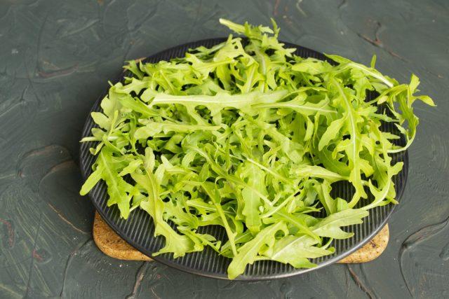 Подготавливаем листья рукколы и выкладываем на большую тарелку ровным слоем