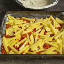 Кладём тонкие ломтики сырого картофеля