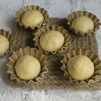 Обминаем тесто, делим на 6 частей, скатываем булочки и кладём в формочки, смазанные растительным маслом