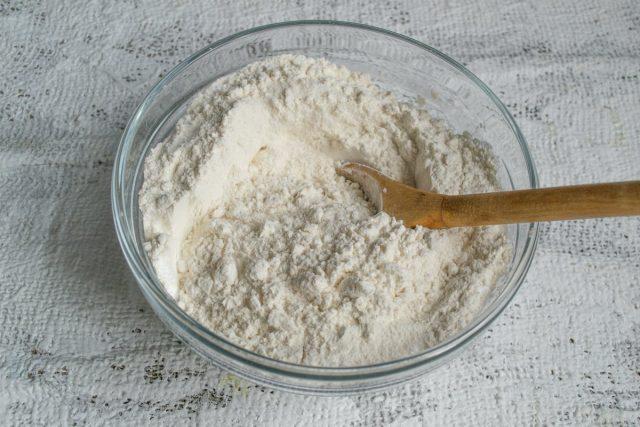 Муку смешиваем с содой и разрыхлителем теста, просеиваем в миску, добавляем сахар, перемешиваем