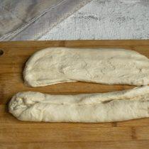 Обминаем тесто, делим пополам и формуем два багета