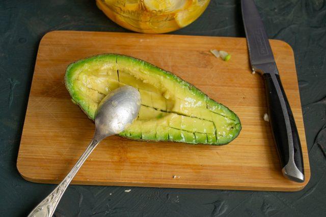Половину авокадо нарезаем мелкими кубиками прямо в кожуре, поливаем соком лайма и выворачиваем