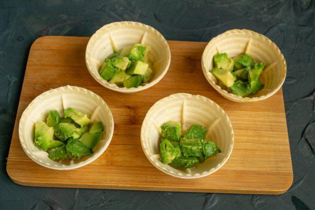 На дно каждой тарталетки кладём порцию авокадо